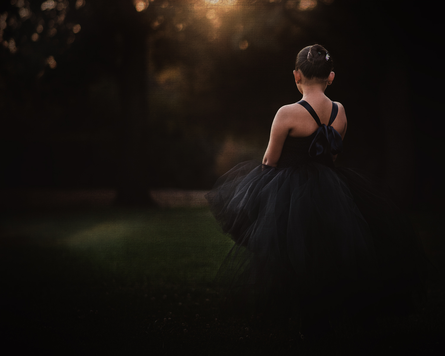 Child model wearing a black tutu dress from Little Ladybug Tutus seen from behind