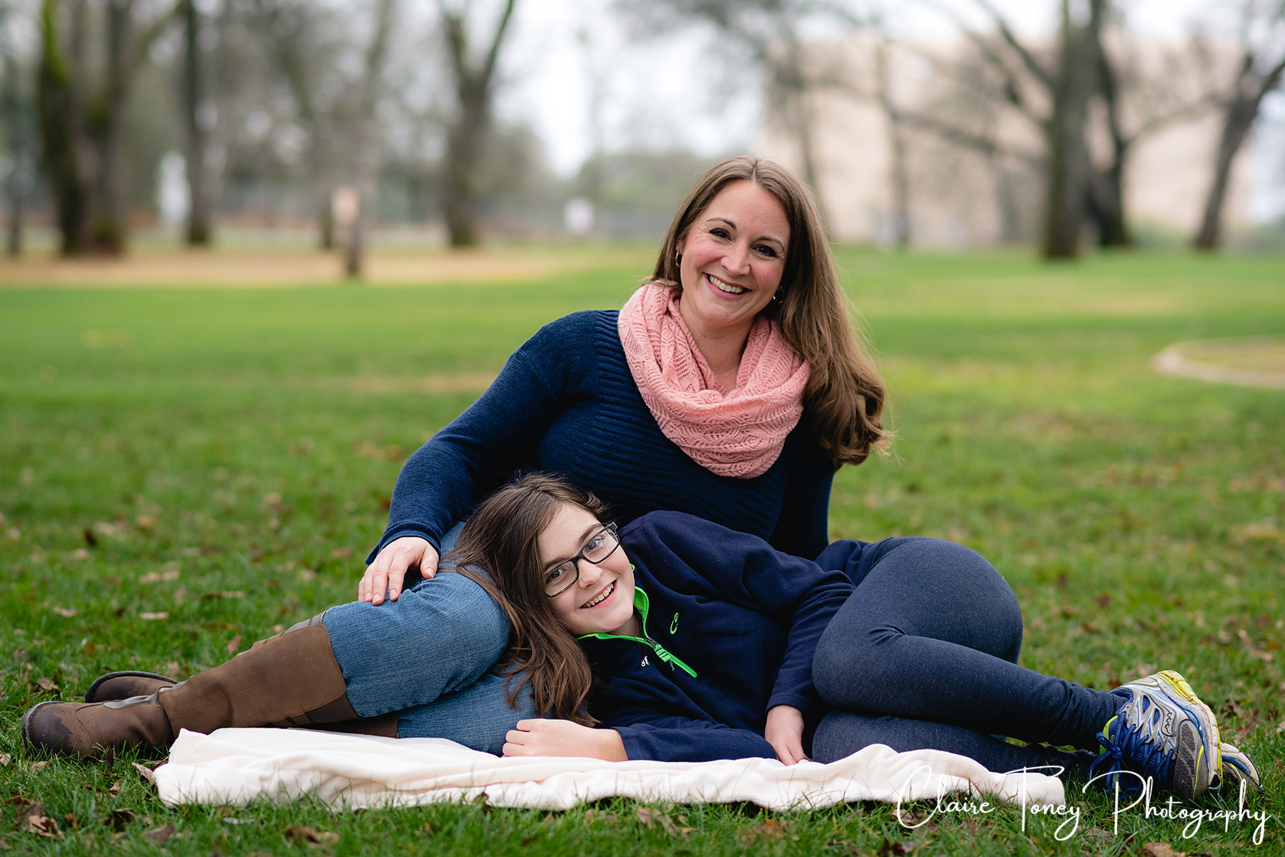 Portrait of mom and daughter sitting at a park