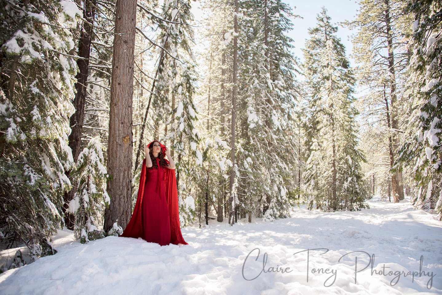 Woman wearing red cape standing in a snowy forest.