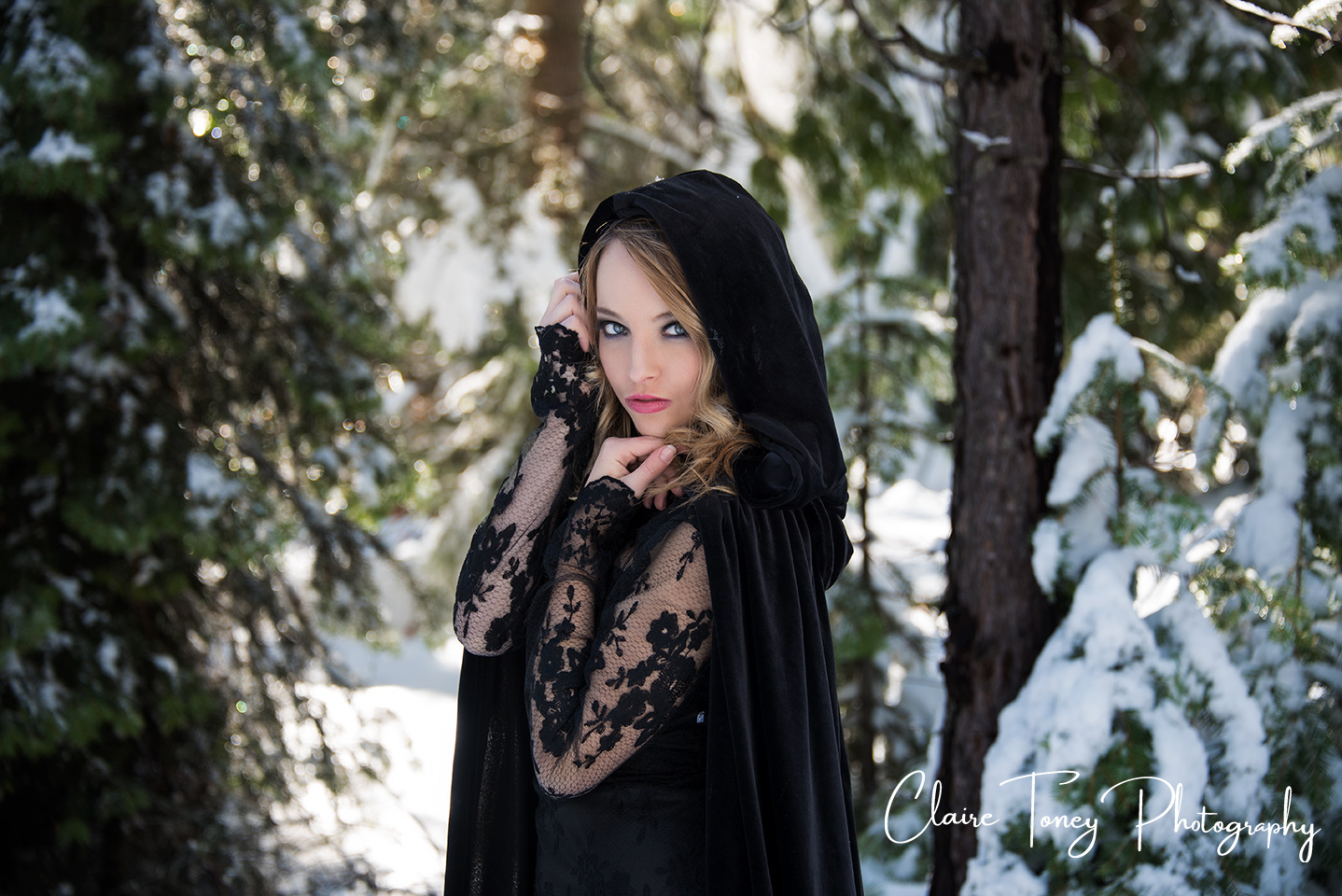 Young woman wearing a black cape and a lacy sleeved dress standing in a snowy forest and looking at the camera