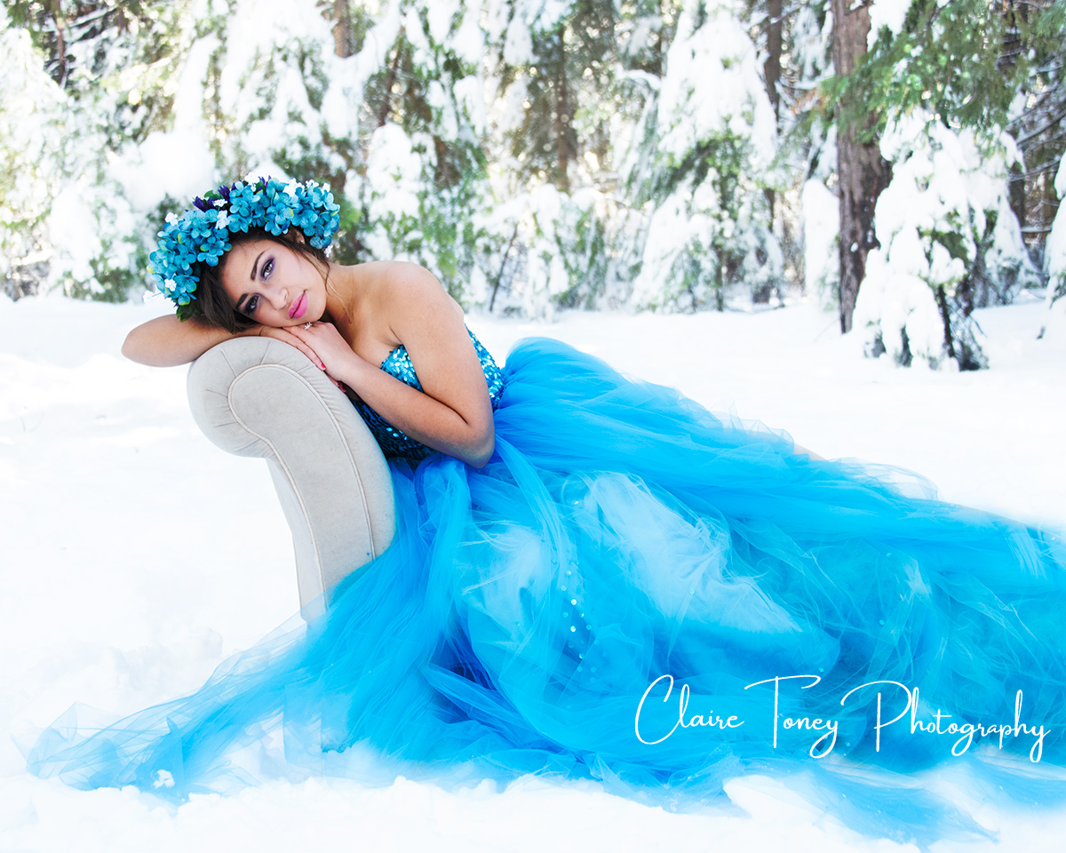 Woman laying on a settee, wearing a bright blue gown, in a snowy forest