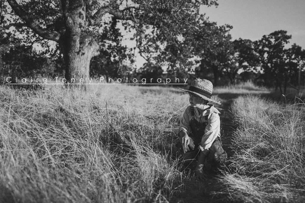 A black and white child photograph of a boy in overalls and straw hat. Claire Toney Photography, Sacramento Photographer