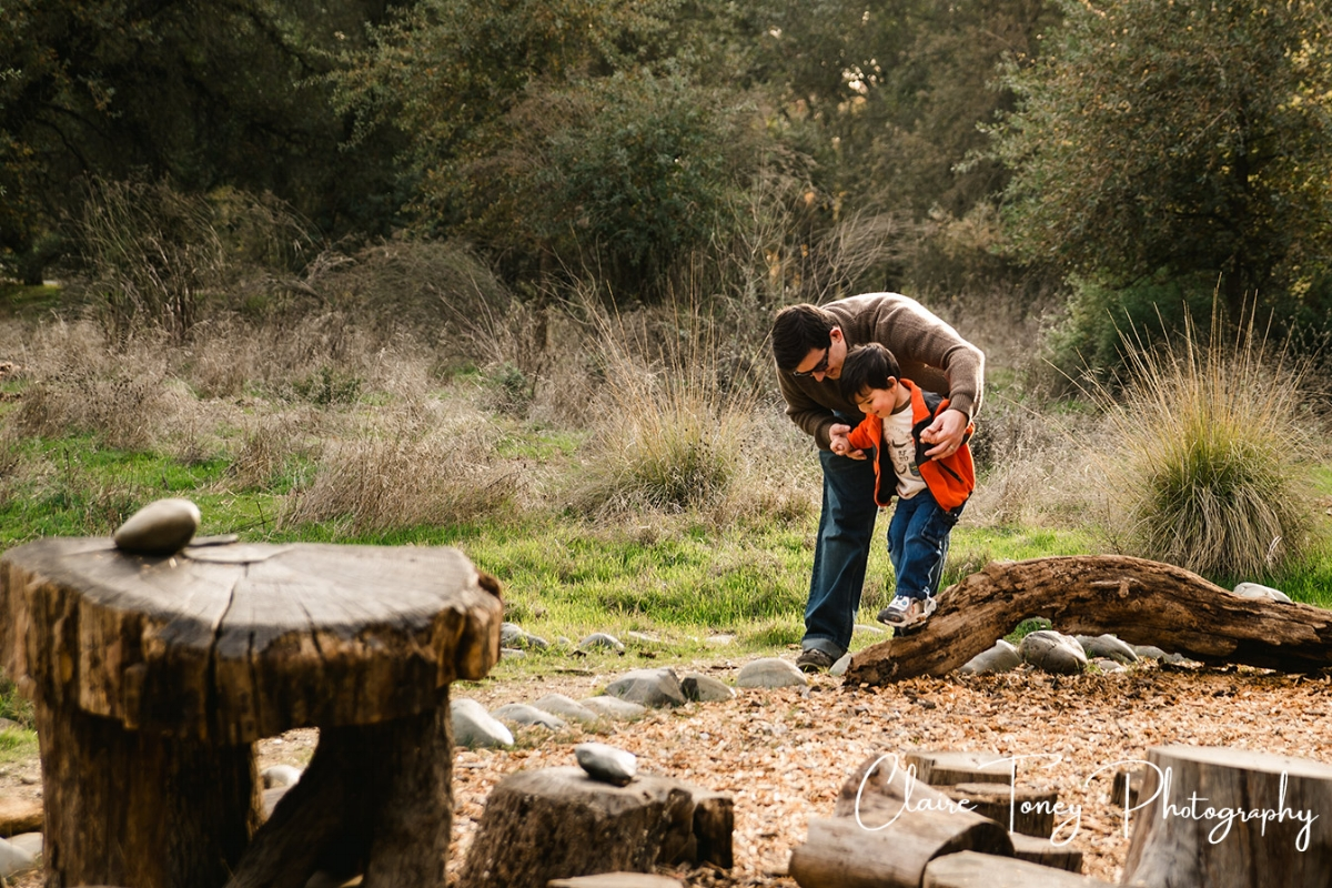 Father helping his young son walk across a log at the Effie Yeaw Nature Center play area