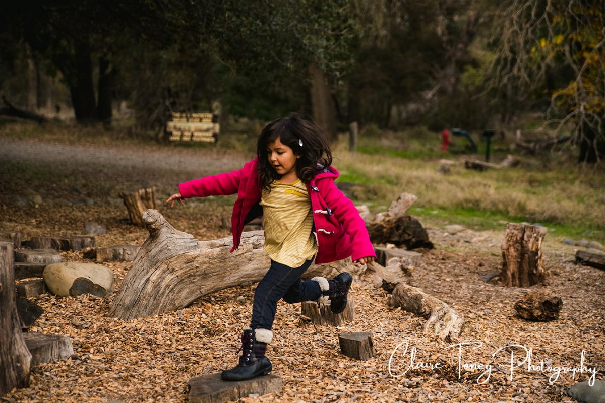 Young girl jumping on logs at the Effie Yeaw Nature Center play area