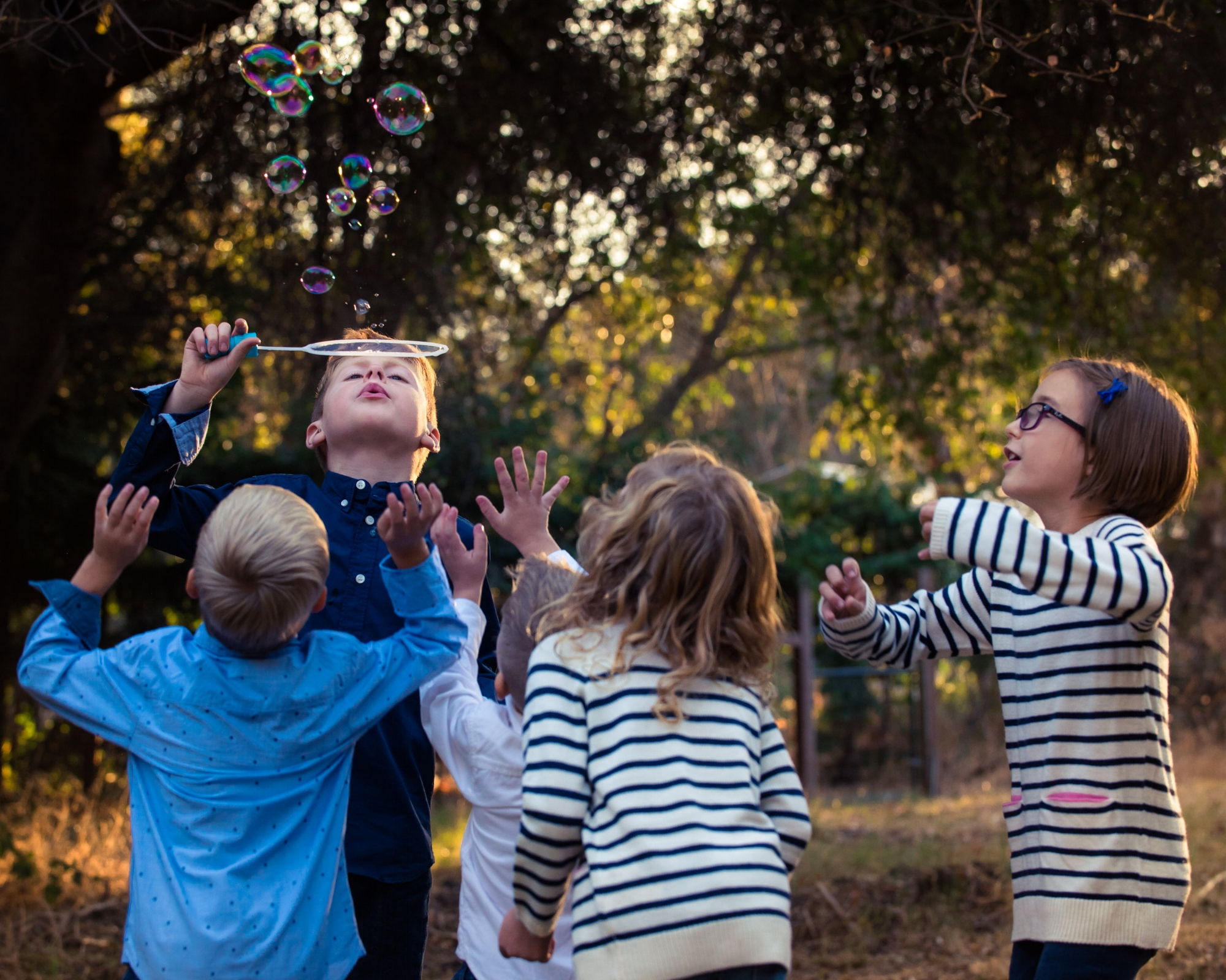 Red haired boy blowing bubble and children surrounding him trying to catch bubbles during a child photo shoot