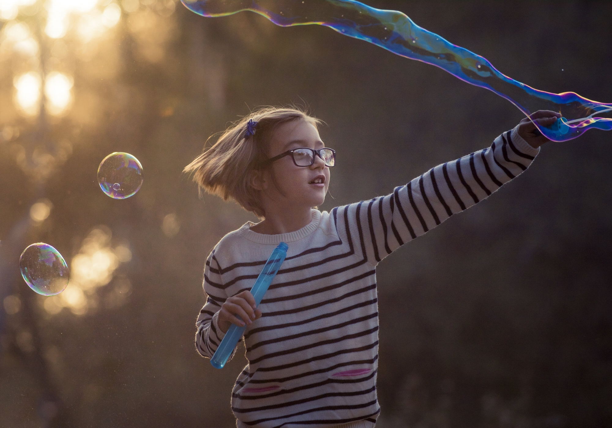 Girl waving a bubble wand with a golden sky behind her