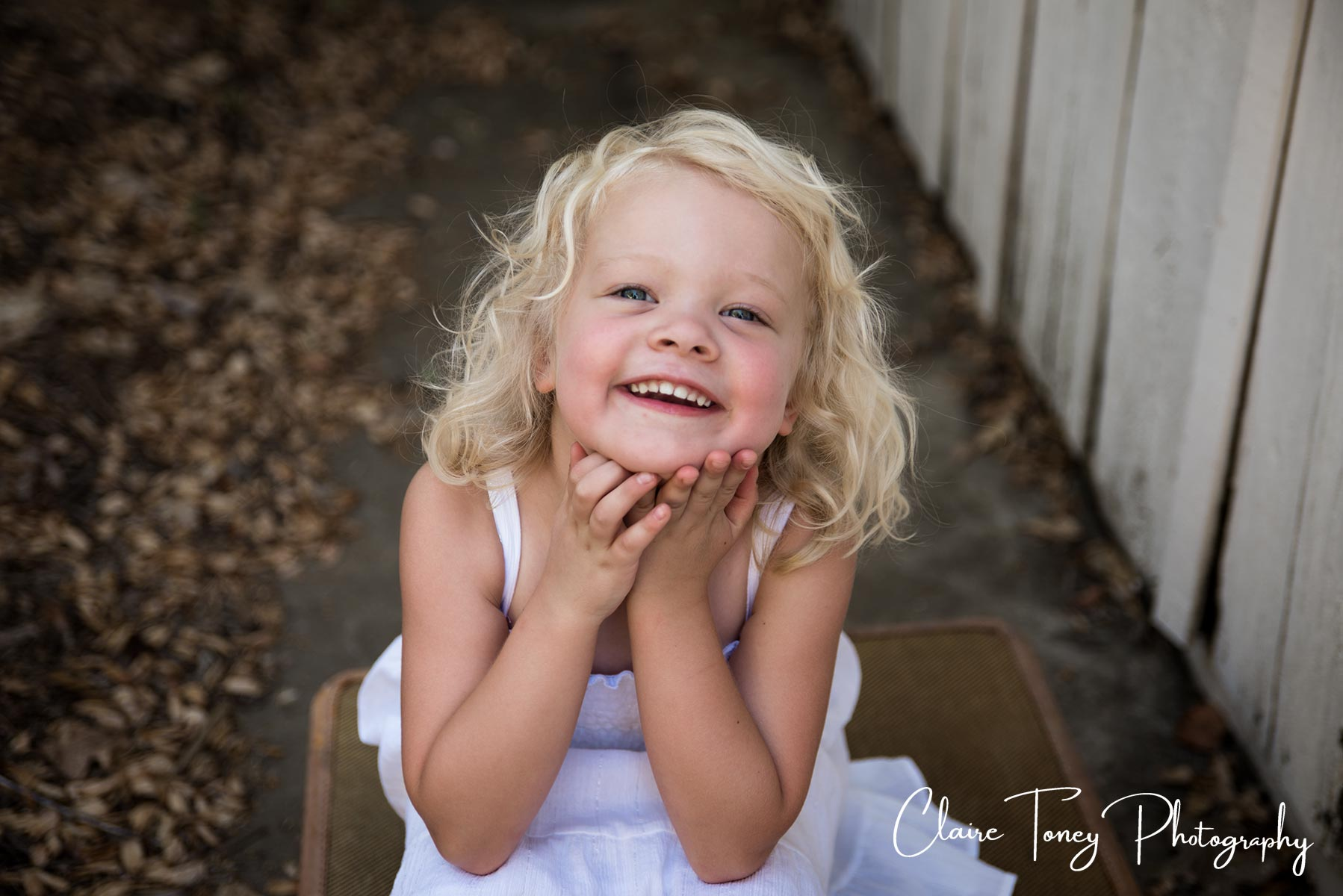 Little girl with her hands under her chin, smiling. Claire Toney Photography, Sacramento Photographer