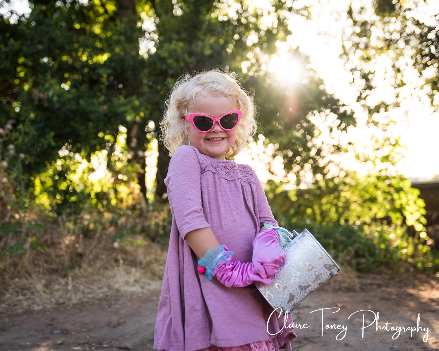 Little girl wearing sunglasses and pink gloves. Folsom CA Sacramento Child Photography. Claire Toney