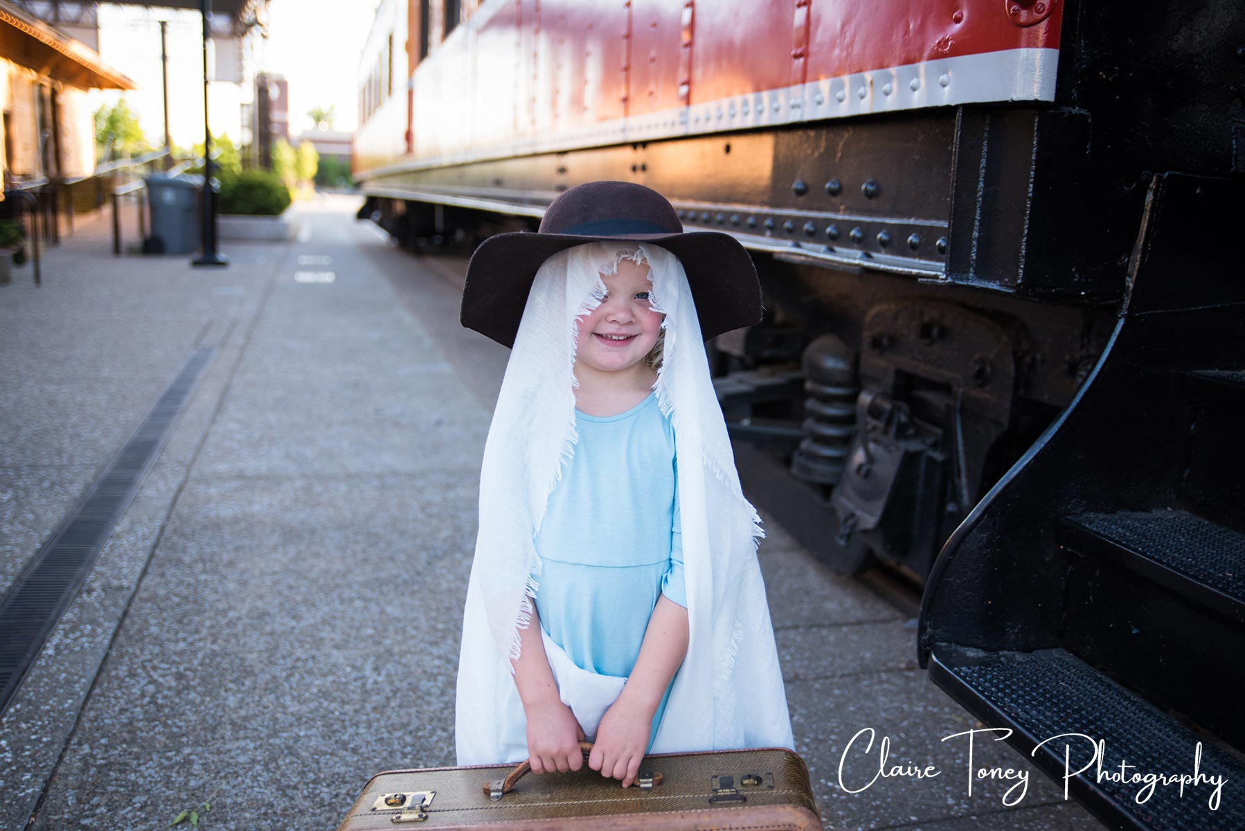 Little girl wearing a hat and a sheet over her head. Child Portraits. Folsom CA Claire Toney Photography