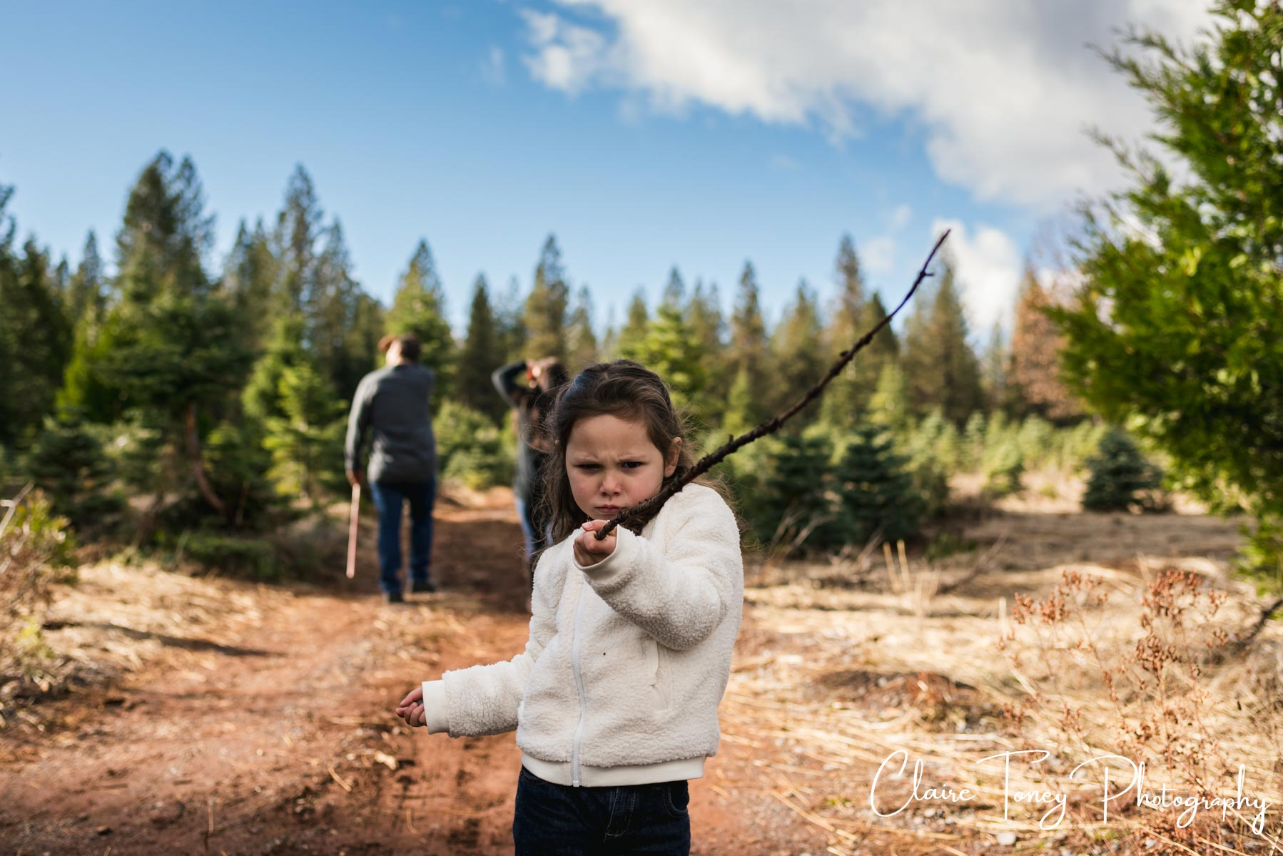 Little girl wearing a white sweater playing en garde with a stick at a tree farm