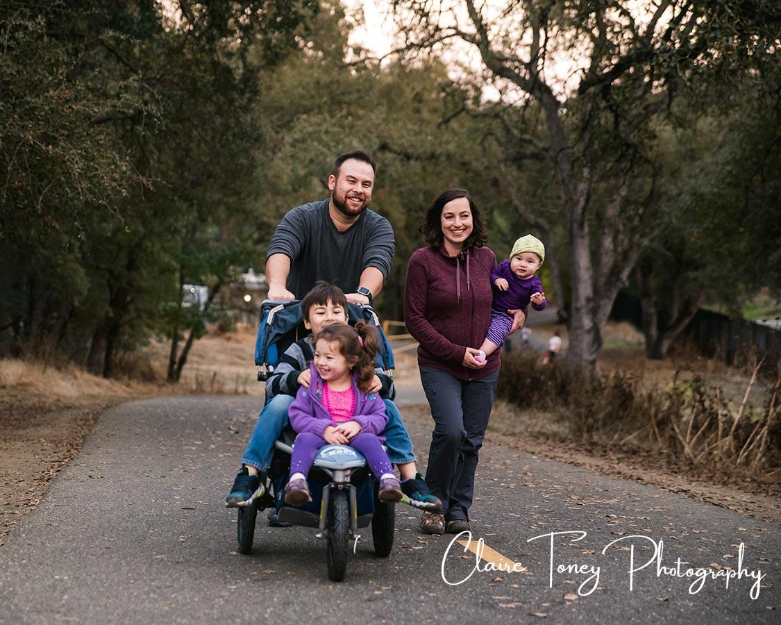 Happy family walking up a bike path