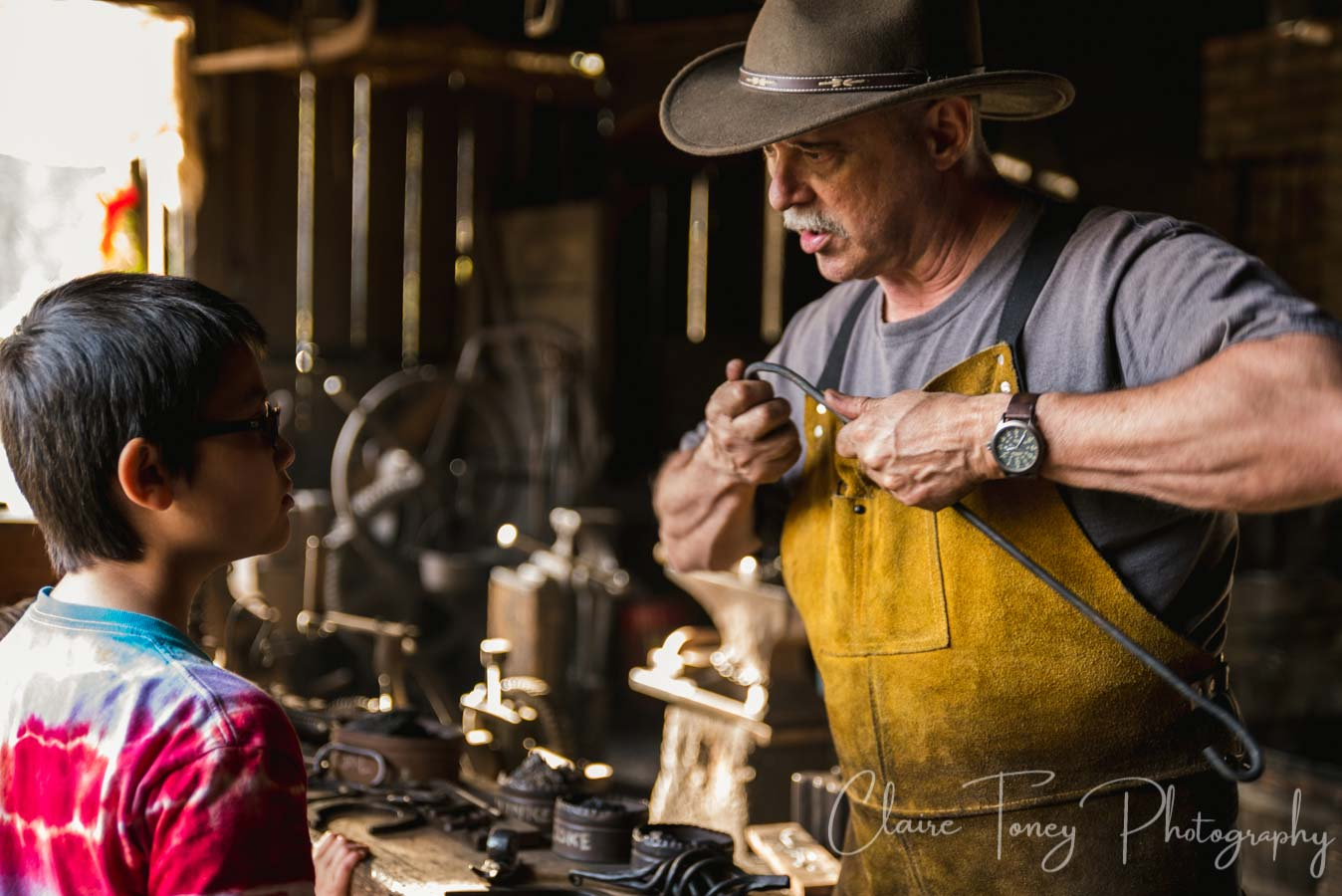 A blacksmith docent at the blacksmith shop where they make everything from horseshoes to home decorations.