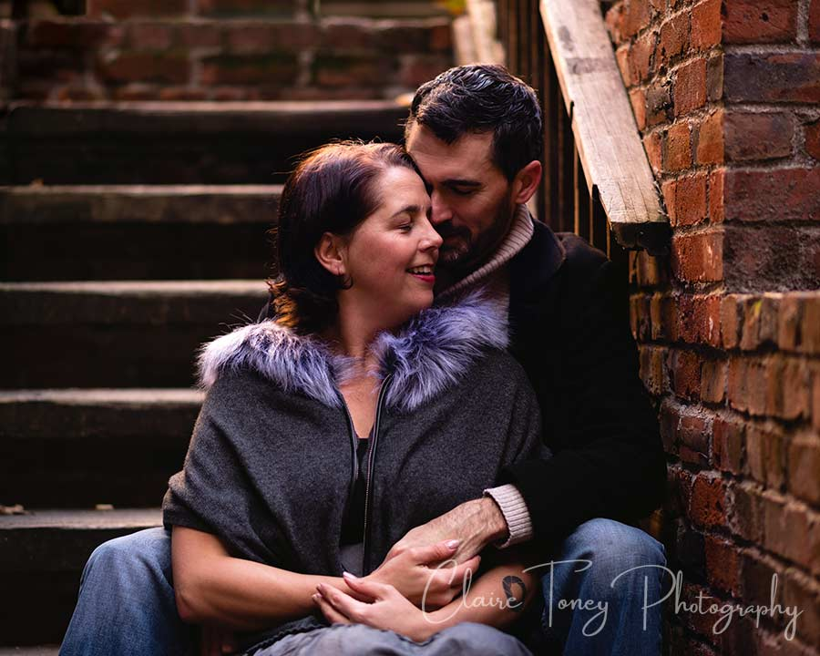 A couple sitting and cuddling on brick steps