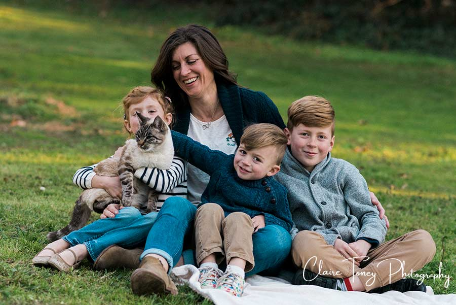 A mom and her 3 children are sitting on the ground with a cat on her daughter's lap
