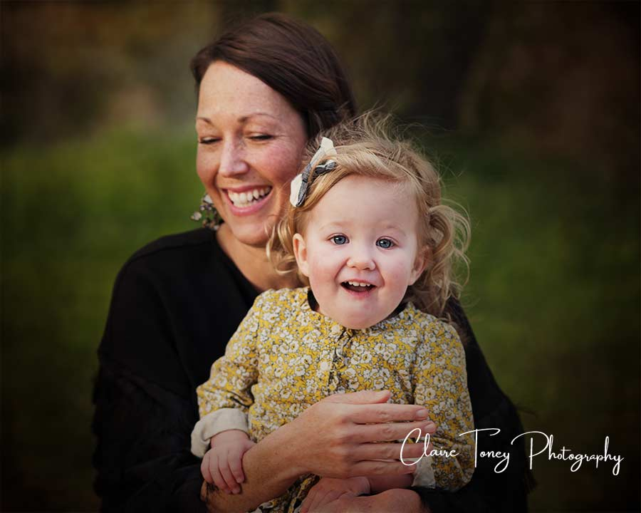 Mom holding her little girl who is smiling at the camera