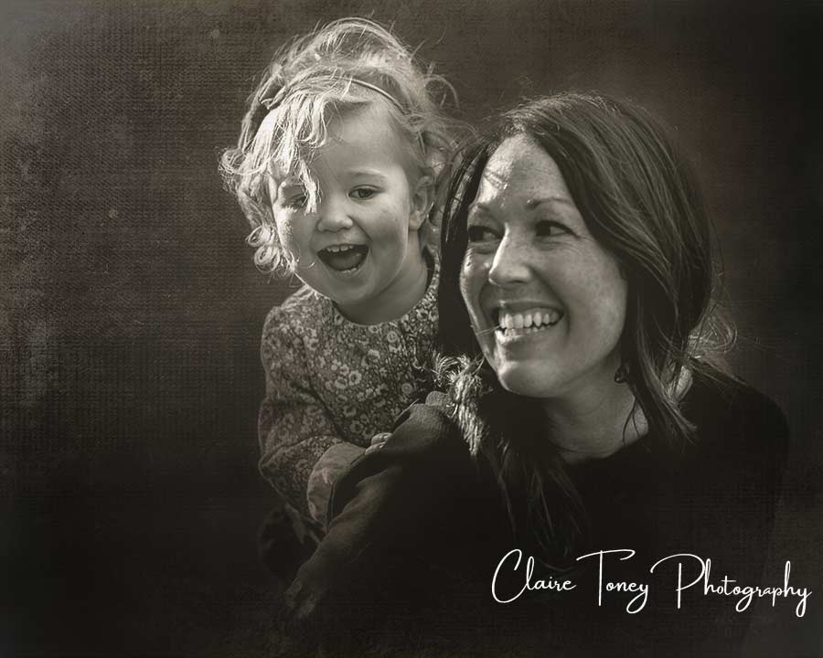 Black and white photograph of a little girl playing behind her mom and both of them are laughing