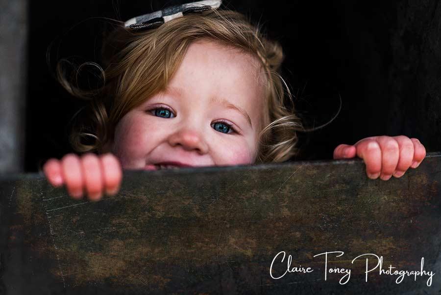 Little girl playing peek-a-boo over a metal rail