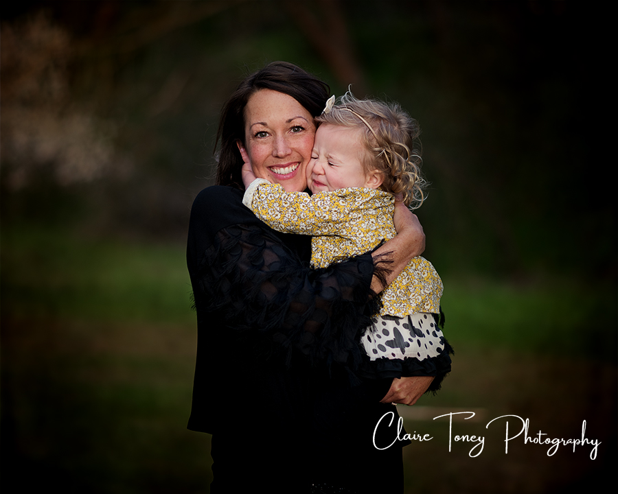 Mom holding her little girl who is squeezing her eyes shut and hugging her mom