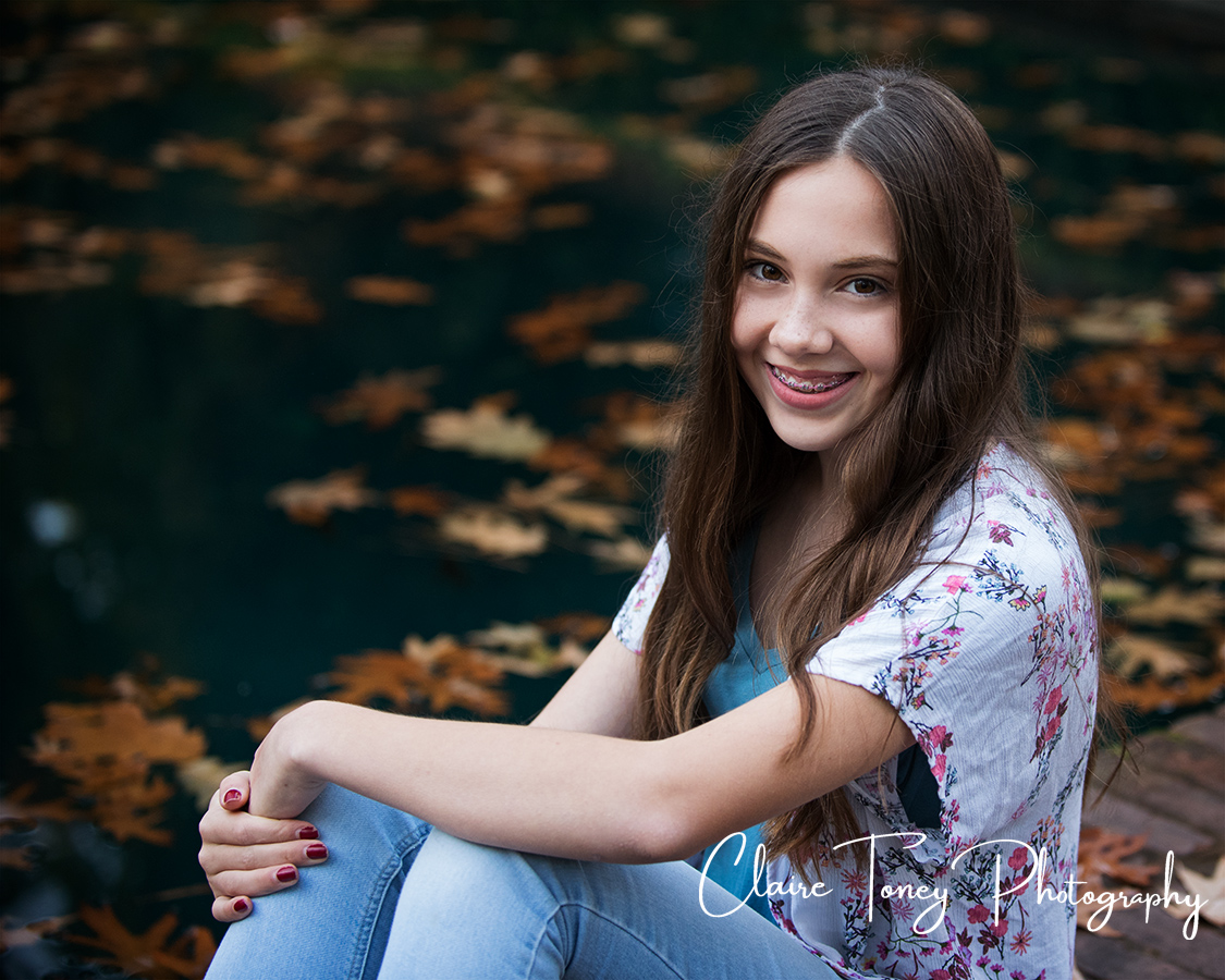 Tween girl sitting in front of reflecting pool covered in leaves
