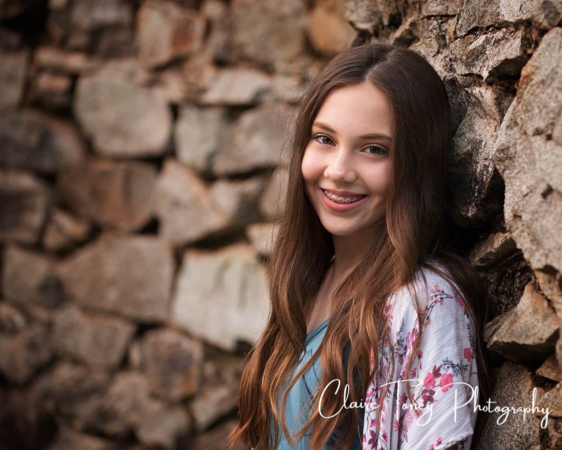 Tween girl leaning against a rough brick wall
