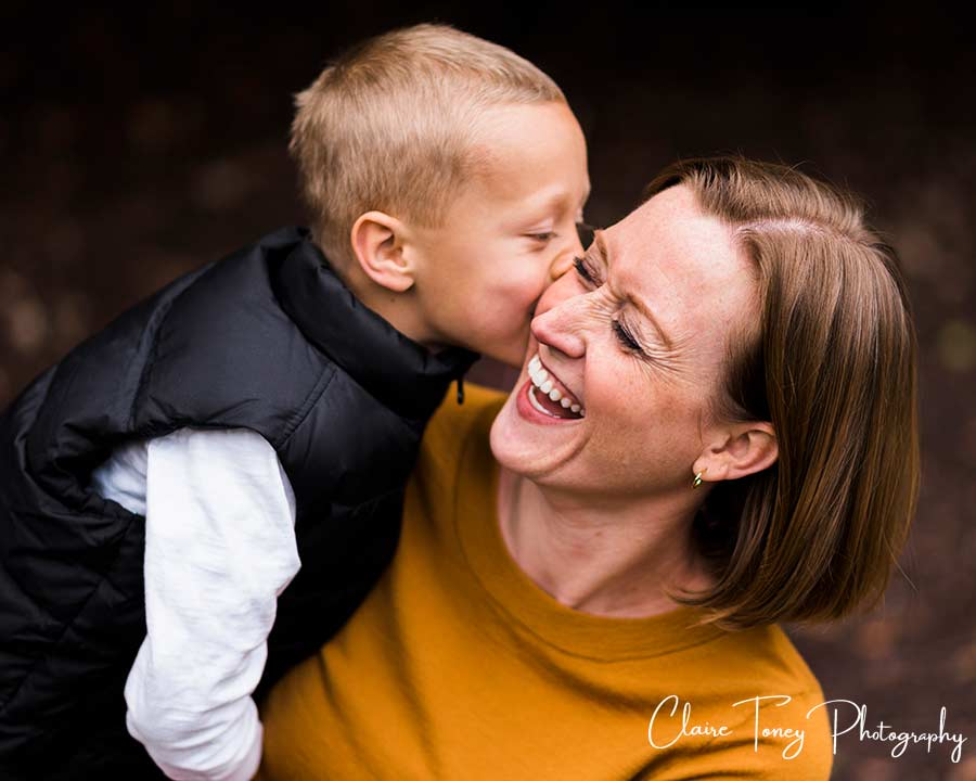 Mom laughing as her son is kissing her on the cheek