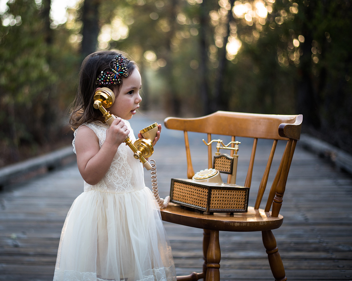 Little girl talking on a vintage phone