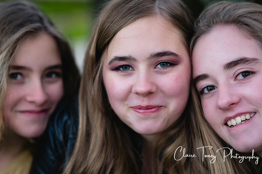 a closeup of three girls smiling for the camera