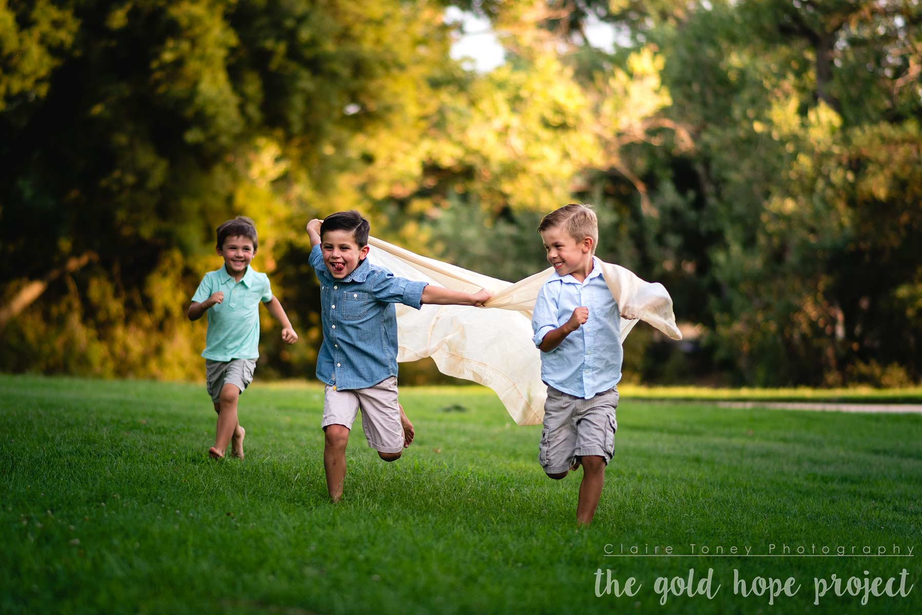 three boys running on a field with two boys holding a cloth behind them