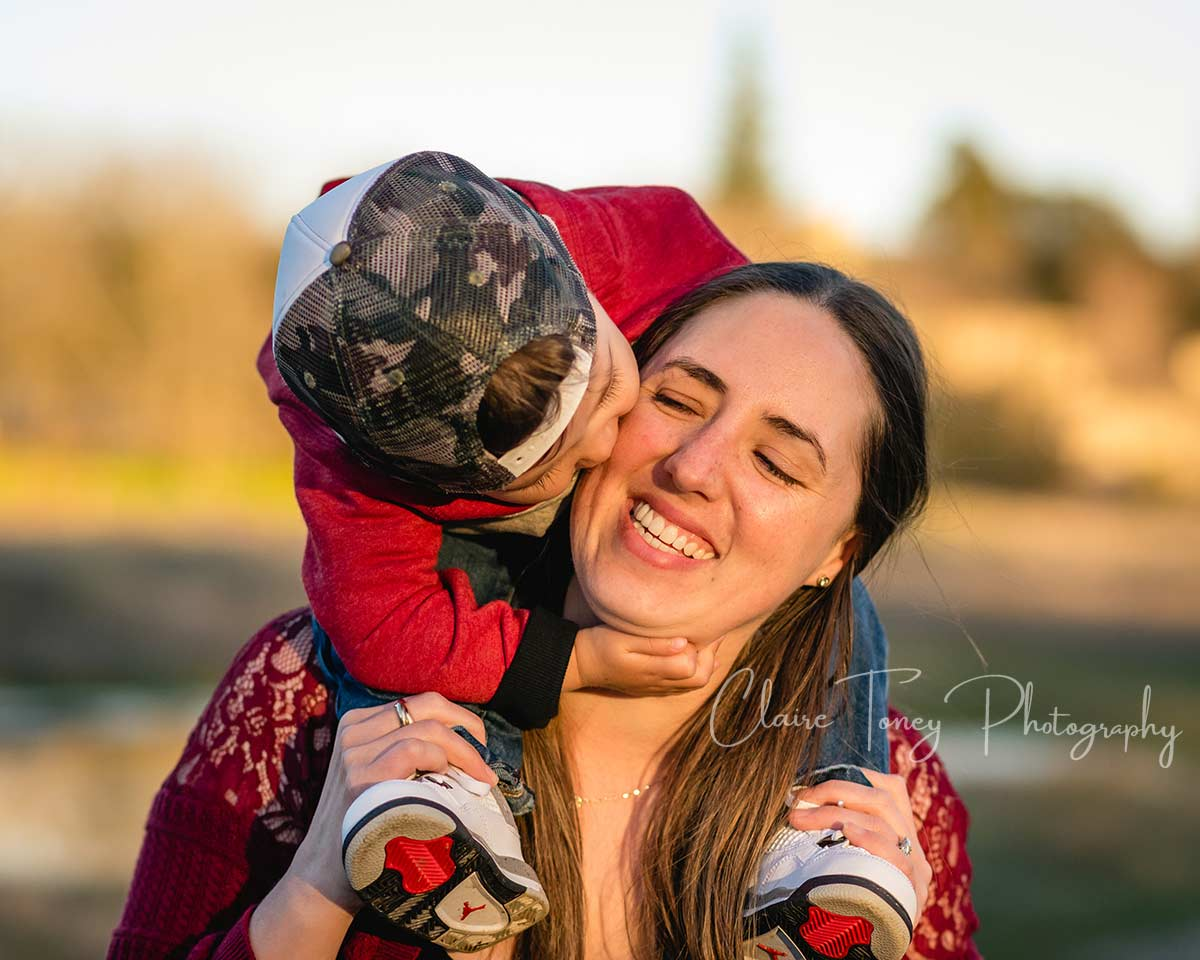 A mom laughing as her son sits on her shoulders and he is giving her a hug and kiss