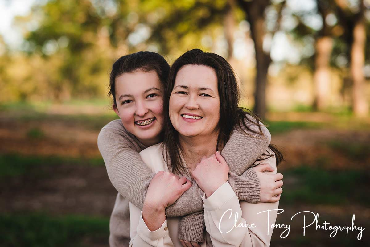 Daughter in braces hugging her mom from behind and both are smiling