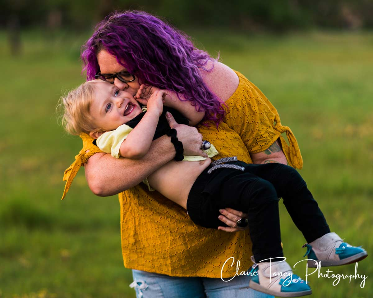 Woman holding, hugging and kissing a little boy who is laughing