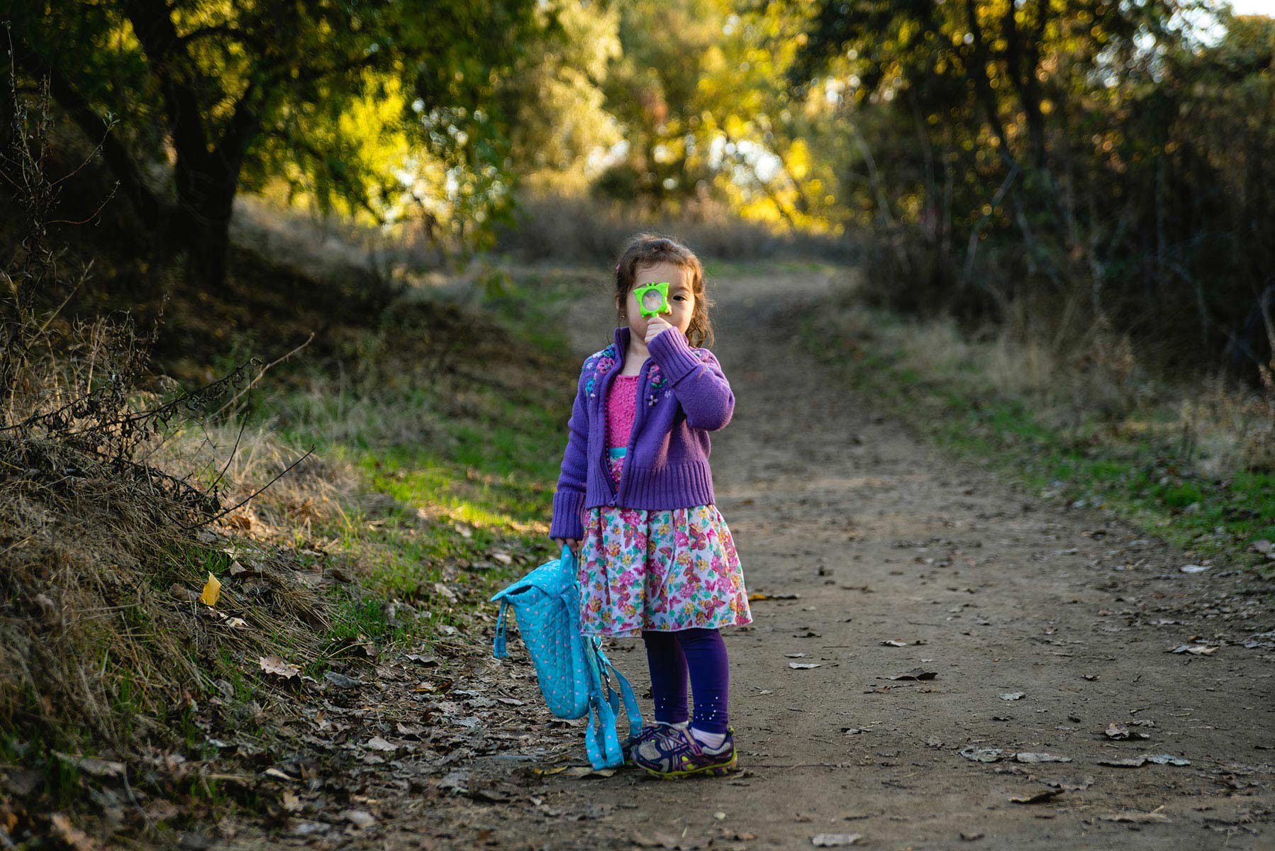 Little girl looking through magnifying glass on a dirt path in Fair Oaks CA