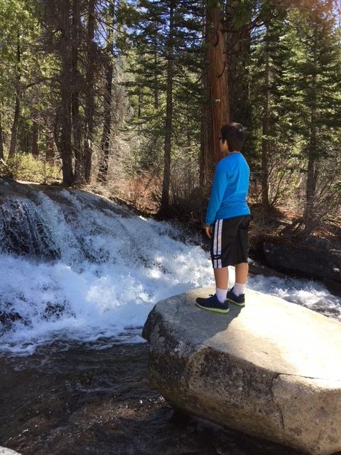 Boy wearing a blue shirt and black shorts with white stripes standing on rock and looking at waterfalls in Pyramid Creek