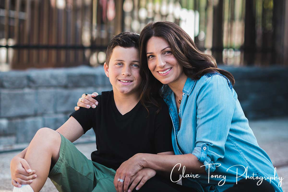 Mother in a blue shirt sitting with her son in a black shirt in Folsom CA