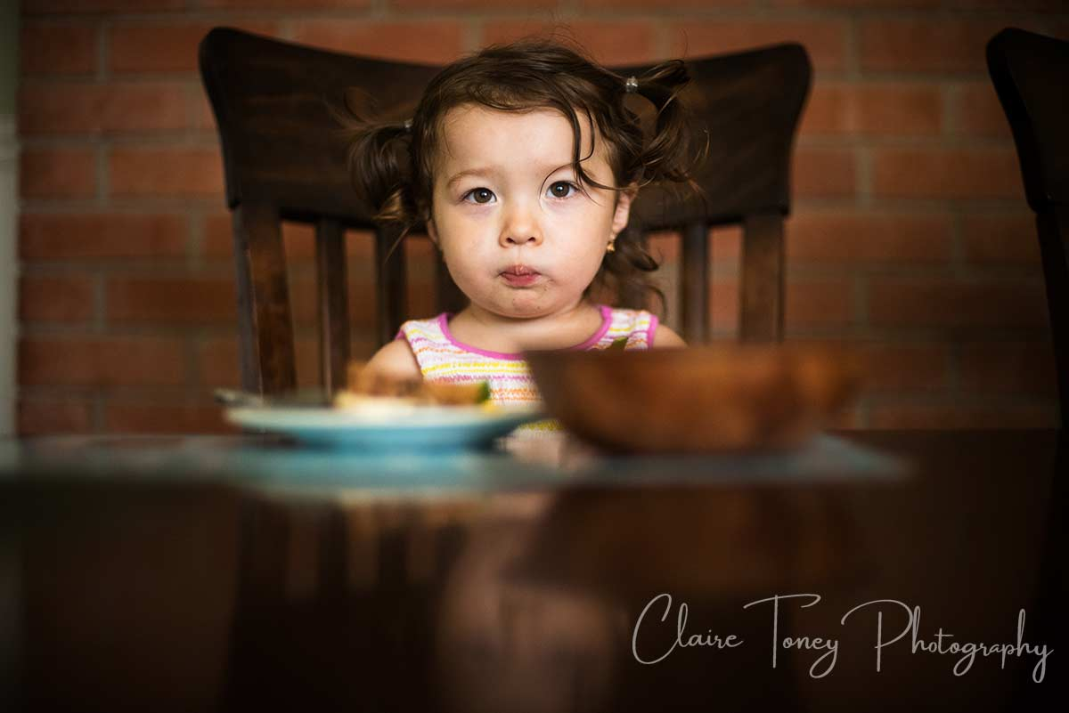 LIttle-girl-with-brown-hair-and-pigtails-eating.jpg