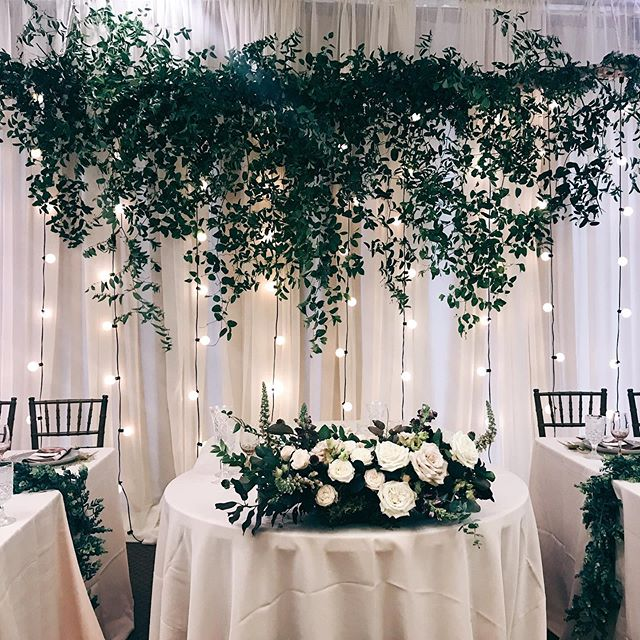One of my favorite head table set ups. A dripping greenery branch, sweetheart arrangement and beautiful lighting!