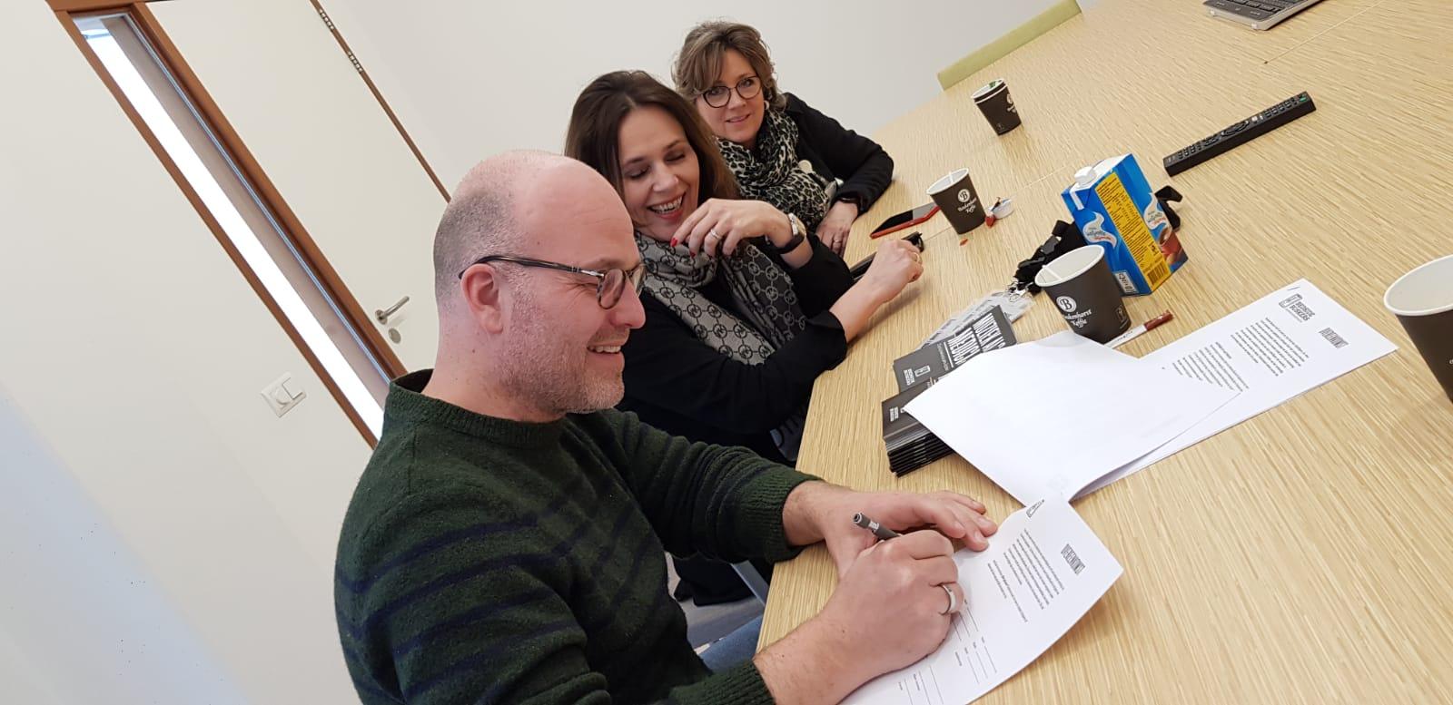 Oprichter Peter Kortleve tekent de overeenkomst (richtlijnen). Naast hem Macha Klomp van Buro voor Muziek.