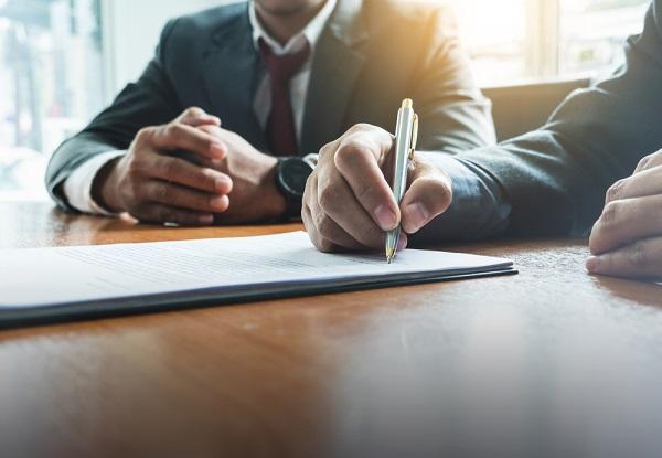 A men writing on an agreement paper