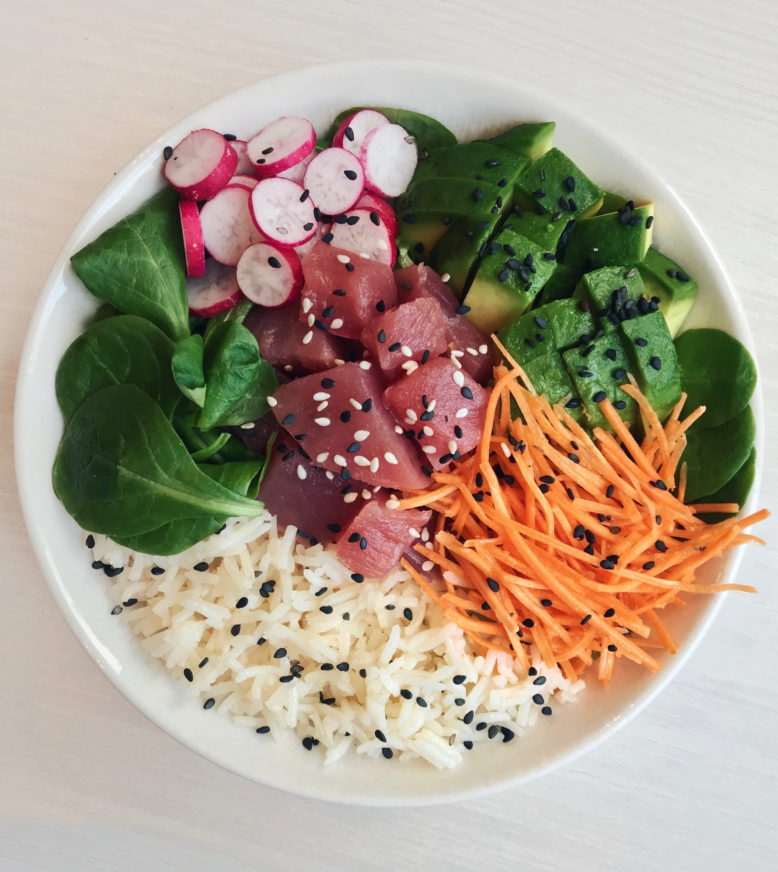 Colorful Fresh Tuna Poke Bowl - What you need:- Basmati rice (boiled for about 20mn)- Fresh tuna (diced)- Avocado (cut into squares)- Pink radish- Carrots (washed and shredded)- Fresh salad leaves- Teriyaki + Soy SauceOnce the rice is cooked, mix it with a soy sauce + teriyaki sauce as well as some sesame seeds. Layer inside your bowl. Dispose all the other ingredients on top, and you're set to eat!