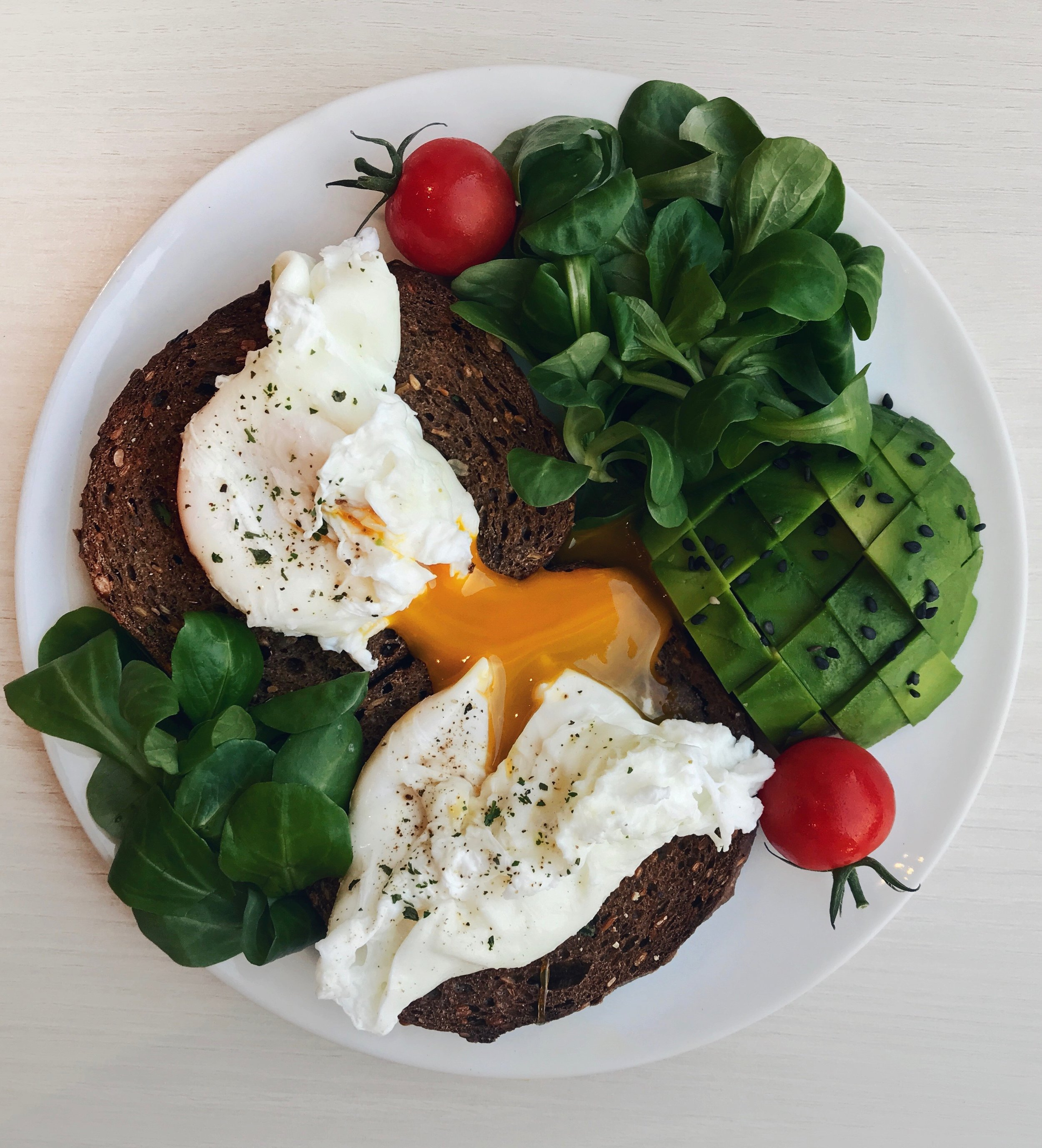 Poached Egg &Avocado Toasts - Toasted nordic bread topped with 2 poached eggs (cooked for about 3min in boiling water with a bit of lemon juice) +parsley +1/2 avocado +leafy greens + cherry tomatoes + black sesame seeds