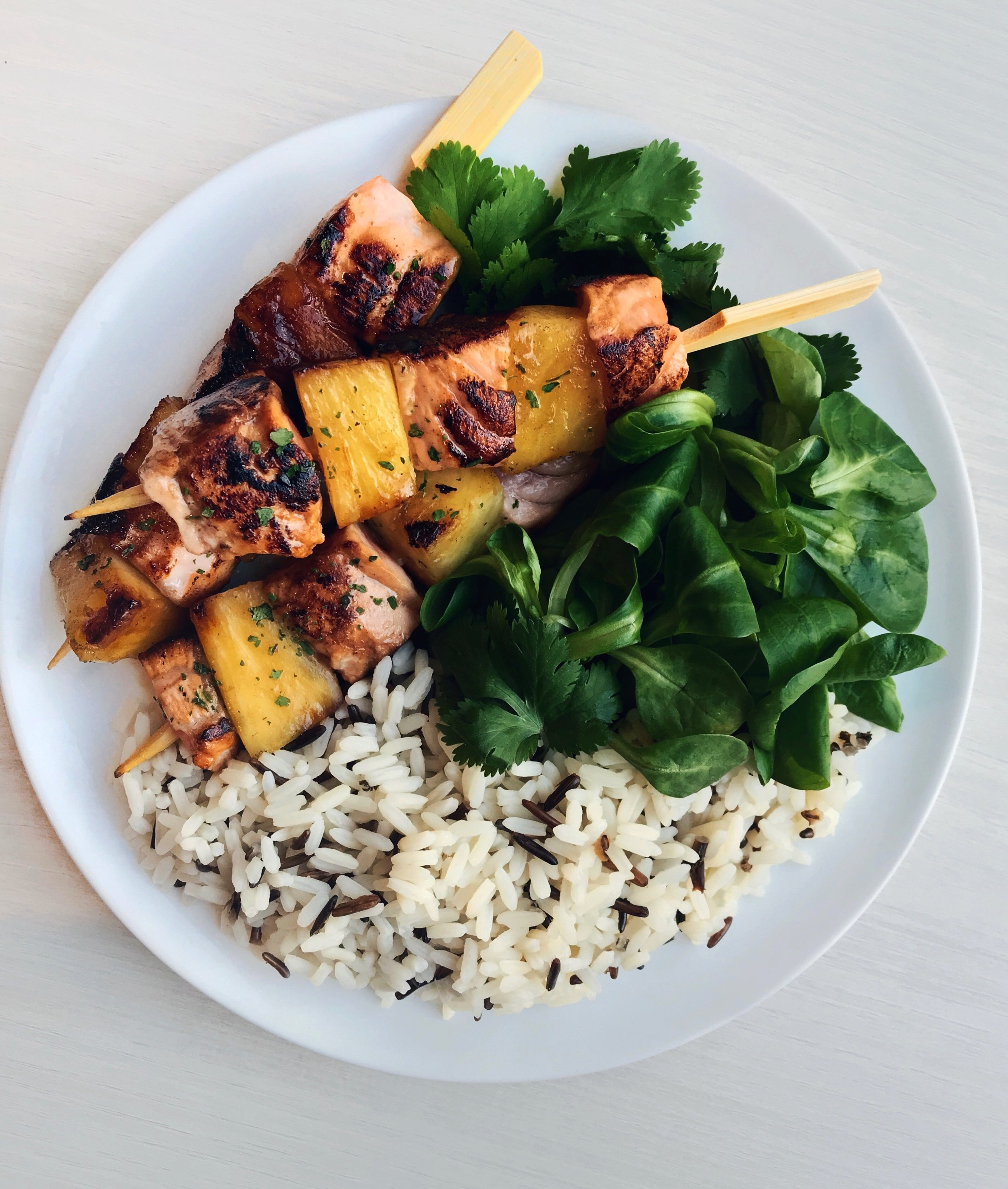 Grilled Salmon & Pineapple Skewers with Wild Rice - Cut the salmon and pineapple into cubes. Put on a skewer and then marinate for about 5min in soy sauce + honey. Grill in the pan on medium heat for just a few minutes on each side + double colored rice + cilantro + salad leaves