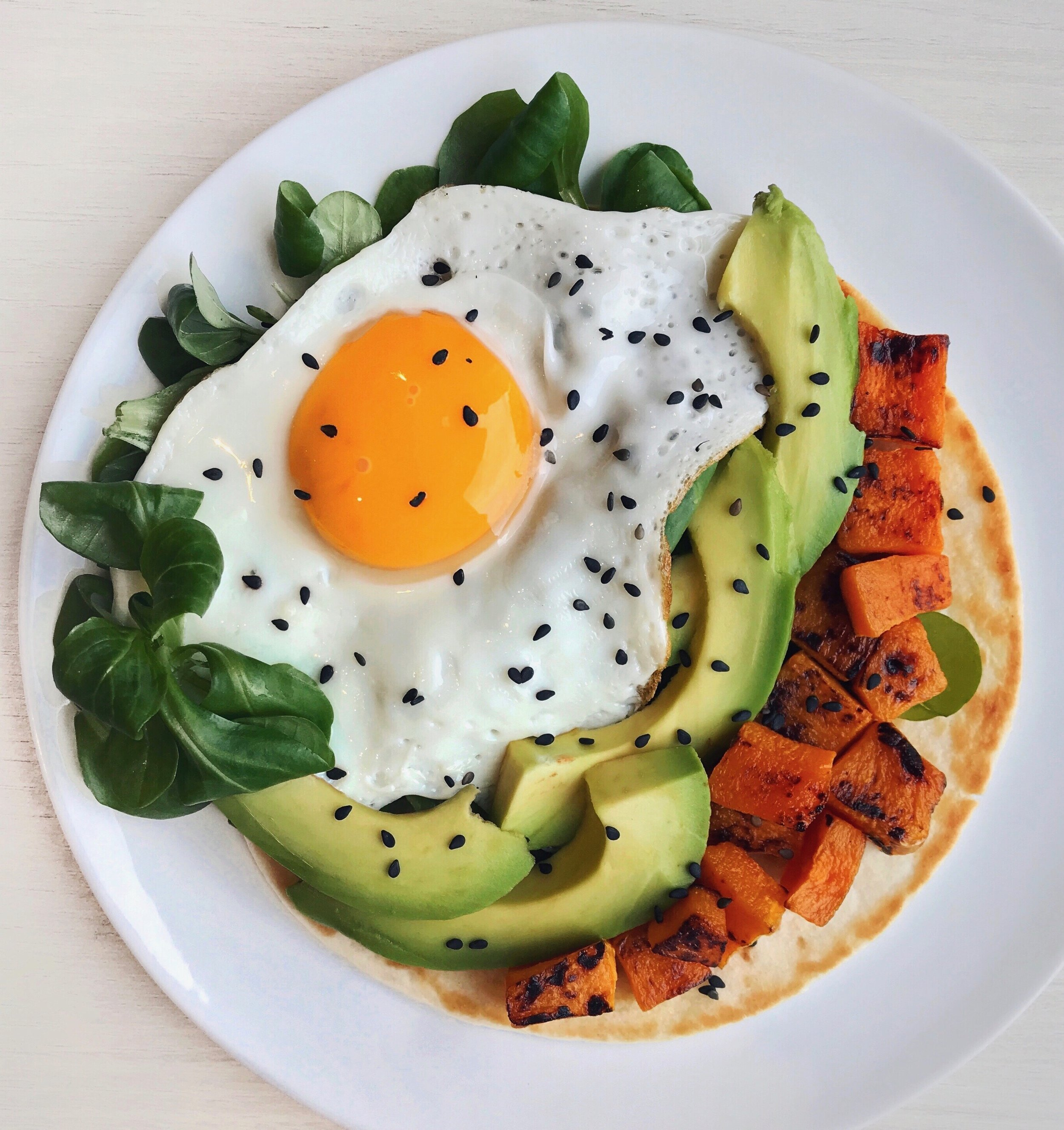 Roasted Butternut, Egg & Avocado Taco - Grilled taco (for about 30s in a pan with a bit of olive oil)topped with roasted butternut squash (in the oven for about 35min at 200C/390C with avocado oil) +avocado slices + fried egg + black sesame seeds +salad leaves