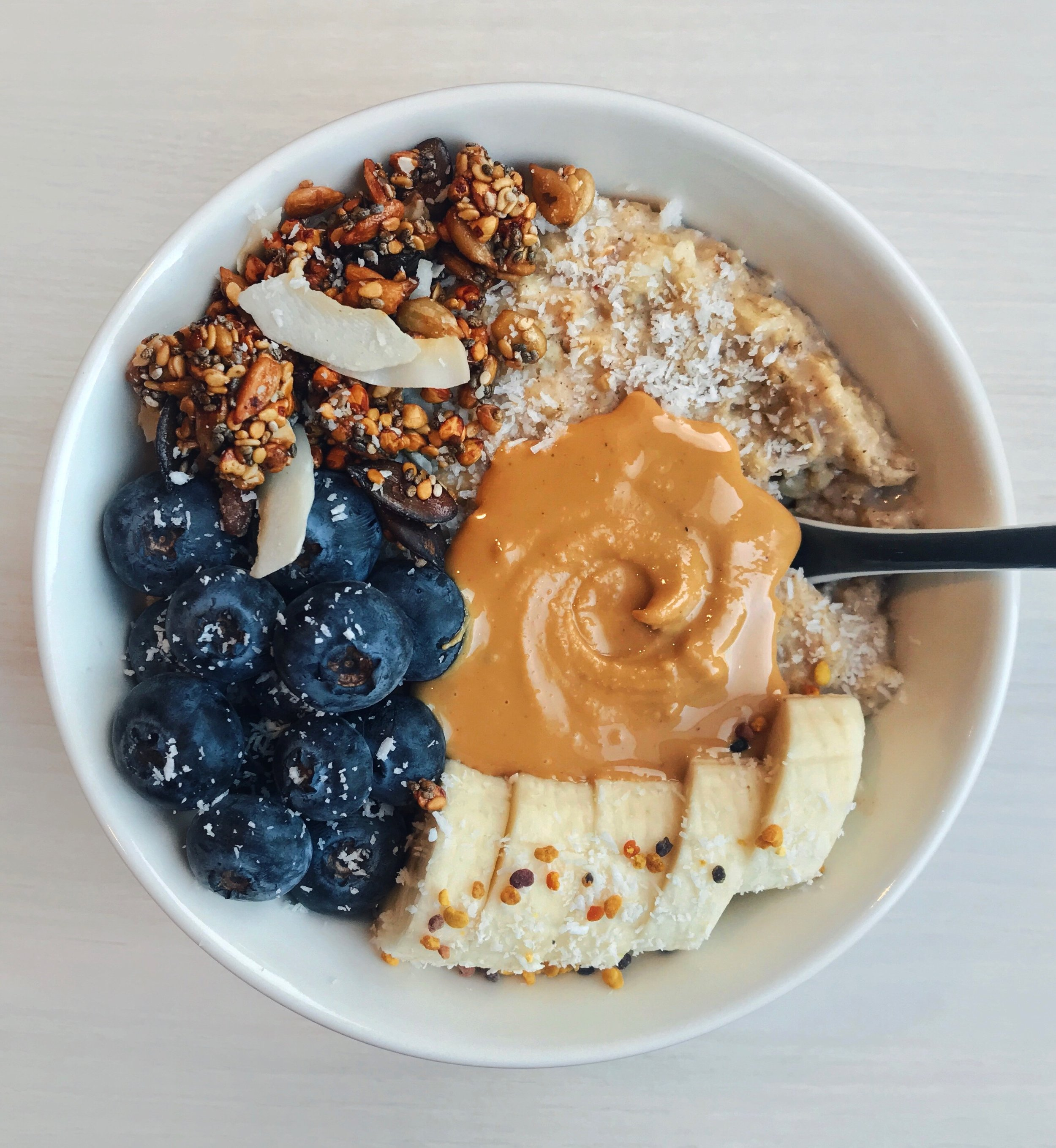 Creamy Coconut& Vanilla Oats - 1/2 cup oats cooked with 1 cup soy milk + 1 tsp coconut powder + 1 tbsp vanilla powder for about 5min on low heat in a pan.Topped with @driscollsberryblueberries +@lameremimosacoconut granola + banana slices +@wild_friendspeanut butter + extra coconut powder +@koro_frbee pollen