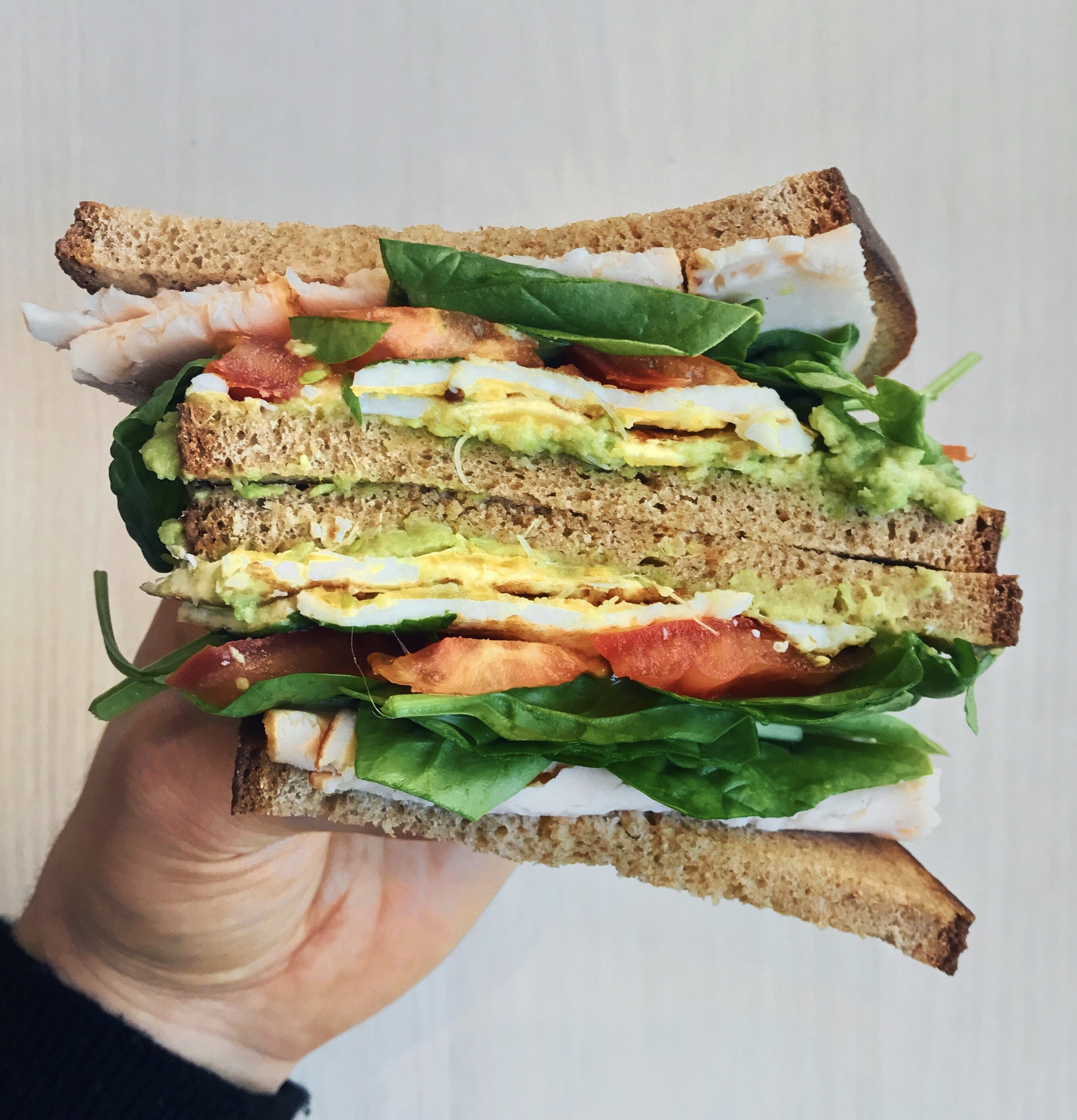 Breakfast & Brunch Sandwich - Toasted rye bread bought with @leshabituesfilled with @naturalia_magasins_biomashed avocado + a fried egg + tomato slices +@florette_francespinach leaves + chicken +@alain_milliatherbs