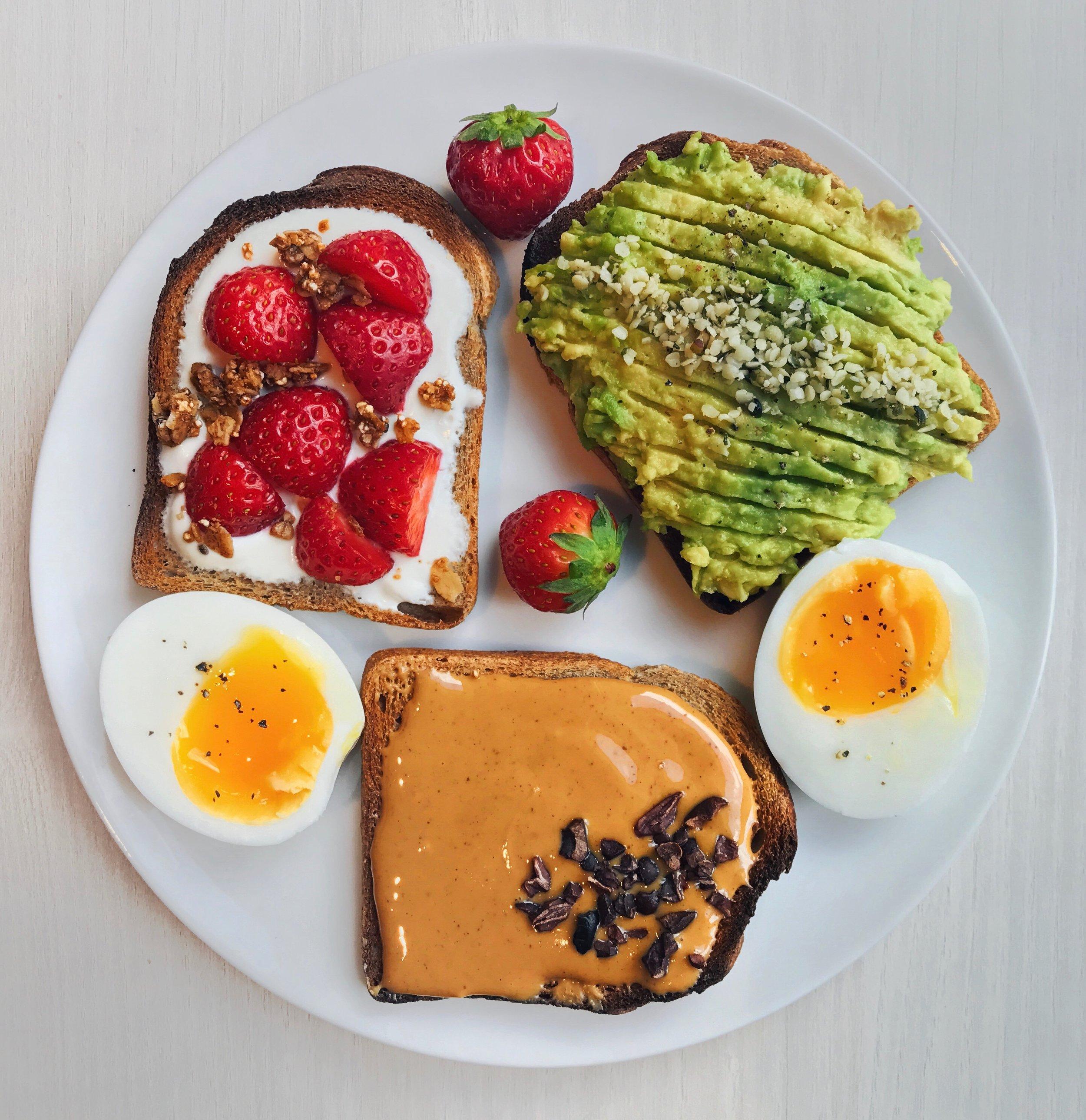 Avocado, Peanut Butter & Greek Yogurt + Strawberry Toasts - Toasted small wholewheat bread topped with 1)@naturalia_magasins_biomashed avocado +@forceultranaturehemp seeds, 2)@crazyrichardspbpeanut butter +@navitasorganicscacao nibs and 3) greek yogurt + vanilla +@driscollsberrystrawberries +@purely_elizabethgranola as well as a soft-boiled egg + black pepper