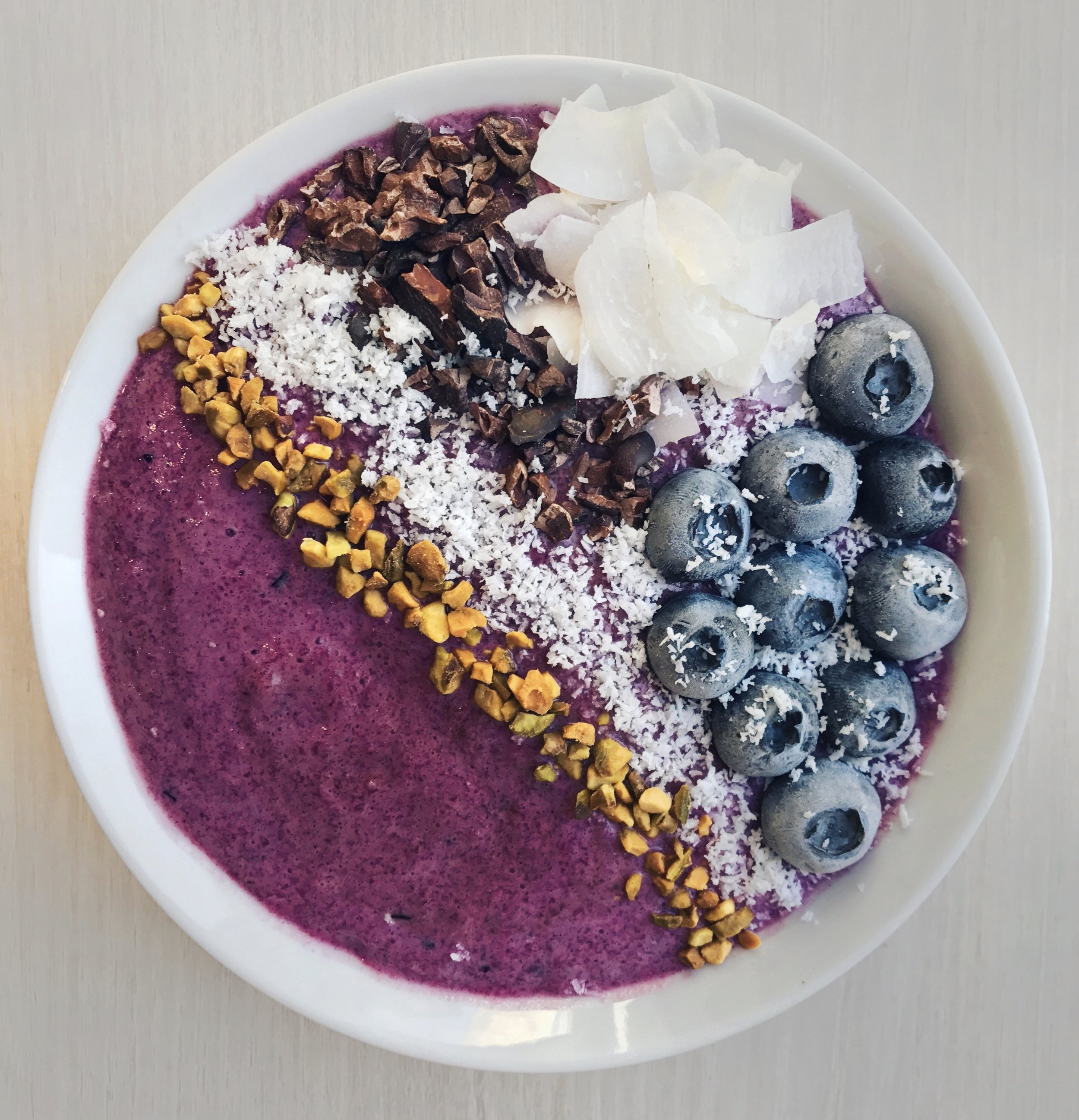 Purple Smoothie Bowl - 2 bananas + 1 cup @driscollsberryblueberries + 1/2 cup raspberries +1 cup of cold beets + 1 scoop collagen peptides + 1 tsp @crazyrichardspbpeanut butter all blended up together.Topped with bee pollen, coconut powder, cacao nibs, coconut flakes and freshly frozen blueberries.