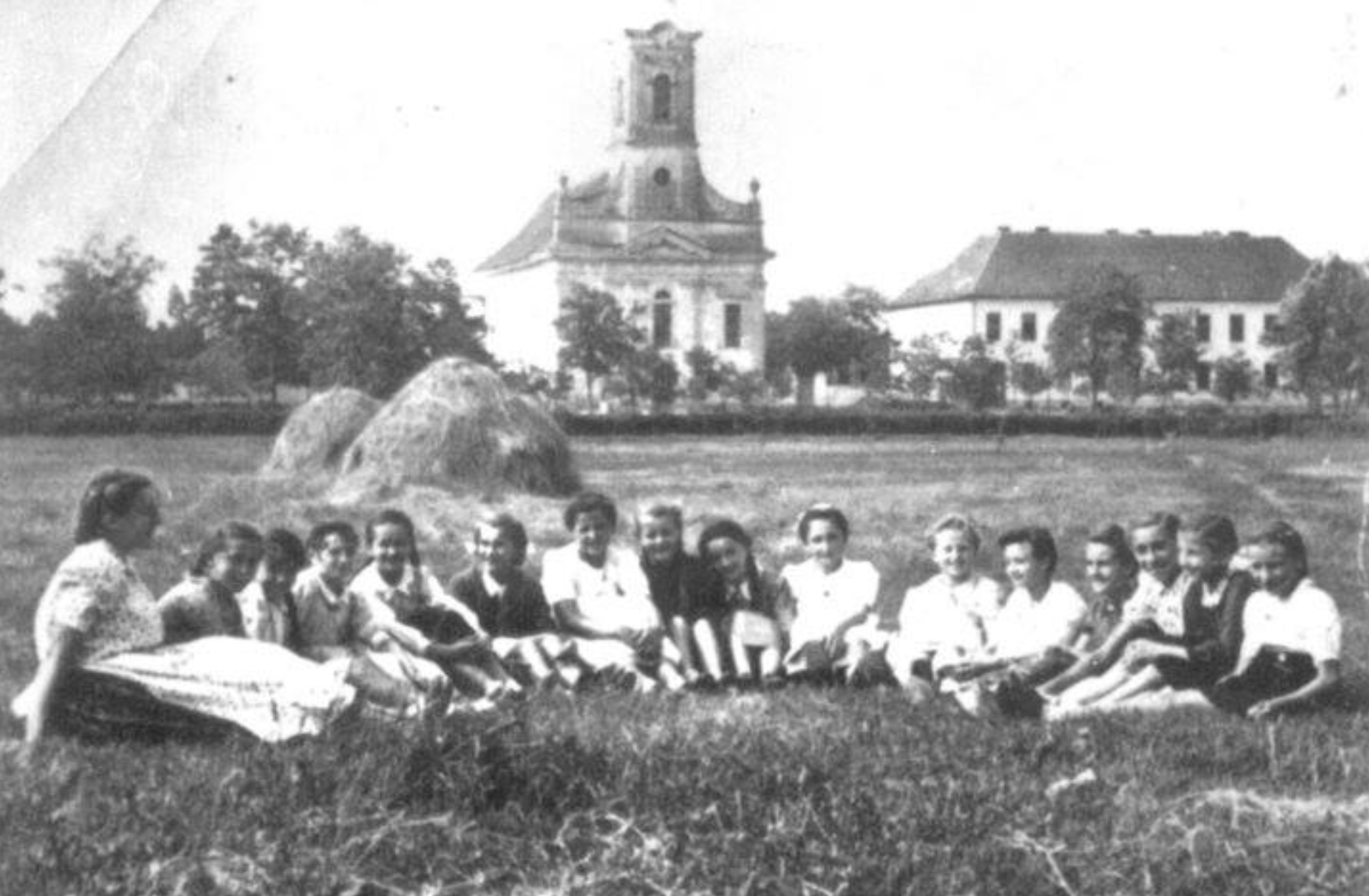 """Group of """"aunties"""" in front of St. Leopold's Kirche (Jabuka, Serbia) early 1940s. This church has been reproduced in our stairway painting by friend Lorrie Quimby, a fellow Yamhill County BB Innkeeper."""