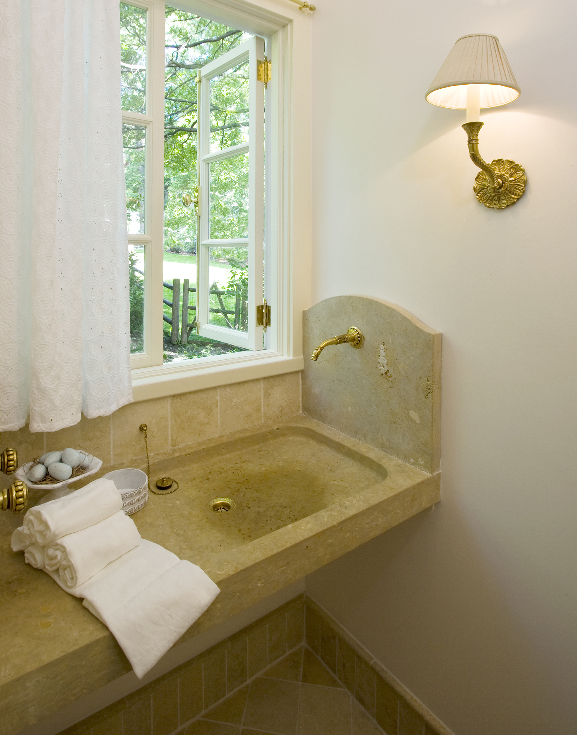 """The Powder Room is truly special. A carved custom limestone sink was designed and built for the client and features a unique wall-mounted faucet. Limestone tile floors and baseboard echo dreams of Roman holidays. Viva l'Italia! """"...heart set on a stone sink like ones she had seen in European farmhouses, but was dismayed by the high price of such items. Thanks to Marvin Clawson, we got a custom-made sink made of native limestone at a fraction of the cost."""" --JSP + JNC"""