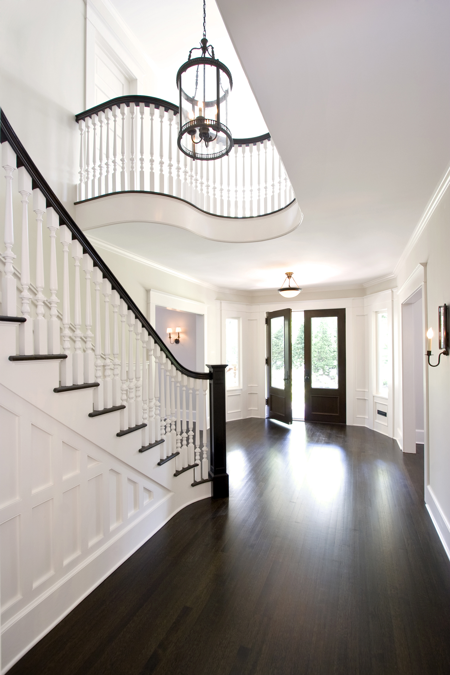 New custom mahogany double front doors with beveled glass detail and side lites enhance the entry foyer experience by giving views into the landscape and allowing natural light in.