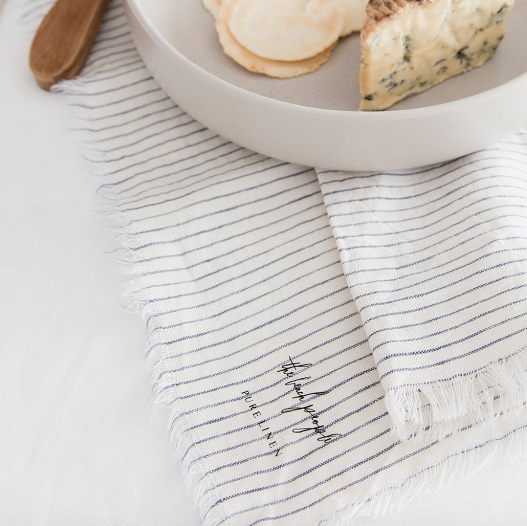 THE BEACH PEOPLE - The Beach People linen is made from the finest flax plants, grown in France. Linen evokes an understated and honest luxury that will add an effortless elegance to your home. Linen napkins shown in blue stripe.